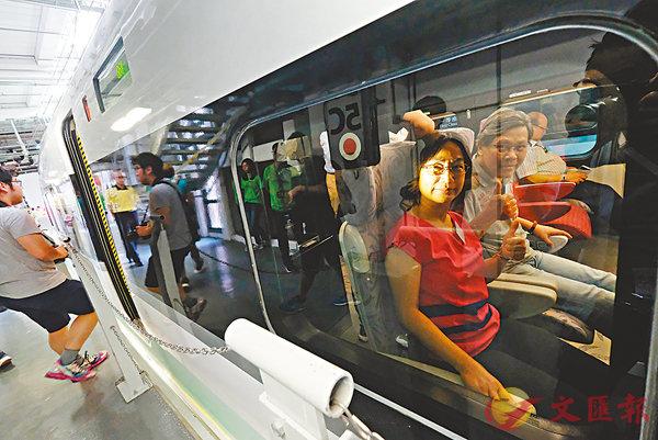 ■體驗乘坐高鐵的市民在車內豎起大拇指讚好。 香港文匯報記者梁祖彝  攝