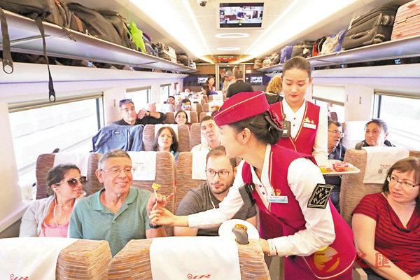 ■在北京南開往上海虹橋的「復興號」高鐵列車上,列車長給外籍乘客派月餅。 中新社