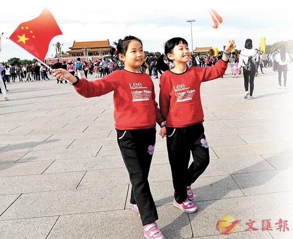 ■10月3日,兩名來自上海的小學生在北京天安門廣場拍照留念,歡度國慶長假。  中新社