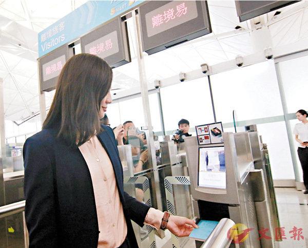 ■旅客離境時,只須把旅行證件的個人資料頁,平放在「離境易」e-道入口的證件閱讀器上,整個出境程序平均只需20秒。 香港文匯報記者彭子文 攝