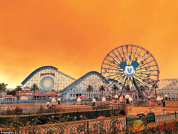 ■加州迪士尼樂園上空被濃煙染成「南瓜橙色」,襯托充滿歡樂氣氛的米奇老鼠摩天輪,儼如詭異的末世景象。 網上圖片