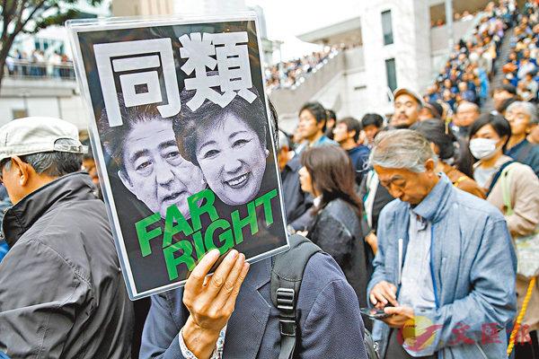 ■東京有示威者舉牌,表示安倍和小池是「同類」。 彭博社