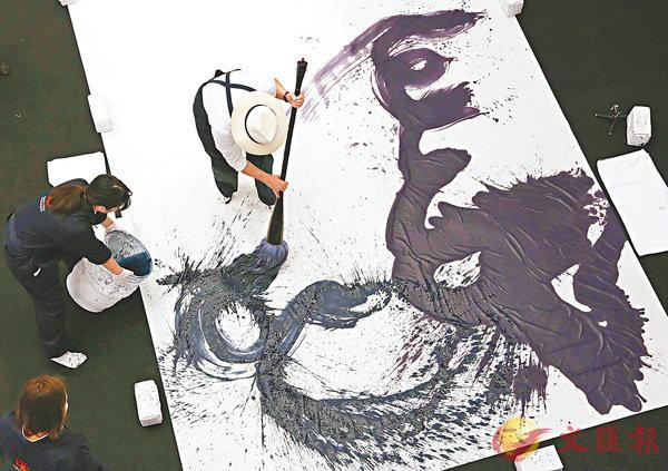 ■陳子慧用特製高大毛筆,在巨型宣紙上以其獨創的書法即席揮毫。 主辦方提供