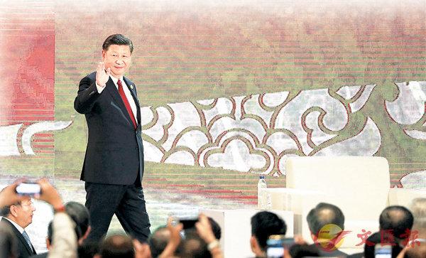 ■國家主席習近平昨日應邀出席在越南峴港舉行的APEC工商領導人峰會,並發表題為《抓住世界經濟轉型機遇 謀求亞太更大發展》的主旨演講。圖為習近平向台下揮手致意。  路透社