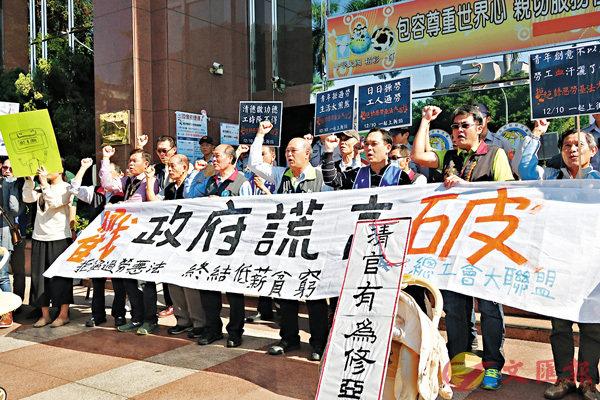 ■高雄市產業總工會、台南市產業總工會等團體昨日到台灣地區行政機構南部聯合服務中心前拉橫額舉牌抗議,促當局停止修《勞基法》。 中央社