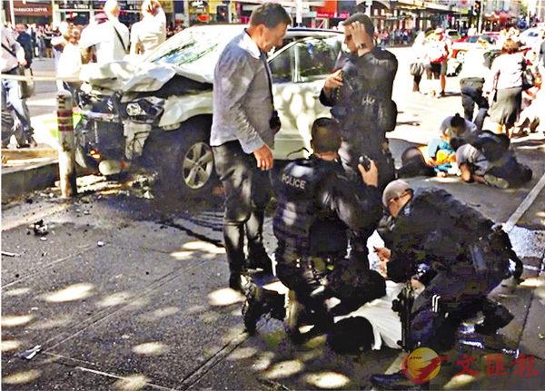 ■兇徒駕車剷上行人路,撞向電車站路障停下,車頭嚴重損毀,穿白衫的兇徒遭警員製伏在地。車輛後方有傷者倒地。 路透社
