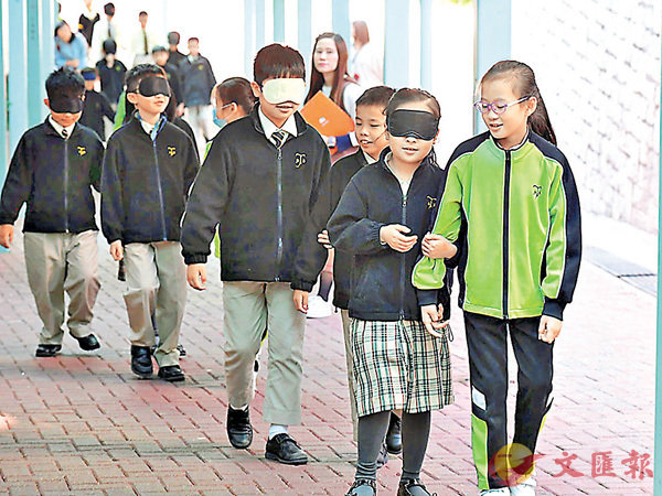 ■學生練習領路法,戴上眼罩體驗失明人士的漆黑世界,並由同伴引領向前走。 政府新聞網相片