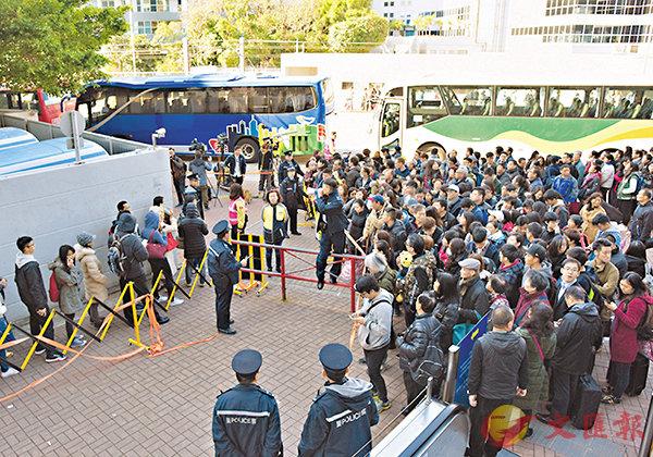 ■當日港鐵九龍塘站外,大批乘客等候接駁巴士,港鐵職員和警員在場維持秩序。 中通社