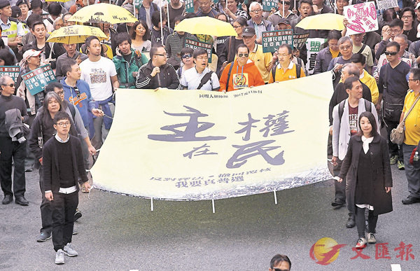 ■ 姚松炎在遊行中走在隊頭(右排二),手持橫額稱「主權在民」。 資料圖片