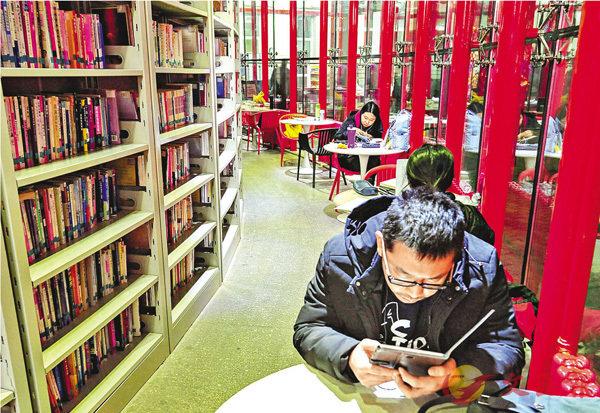 ■ 電子閱讀的時代,「四大名著」仍十分受歡迎。圖為內蒙古呼和浩特市的24小時自助圖書館內,民眾手捧電子閱讀器。資料圖片