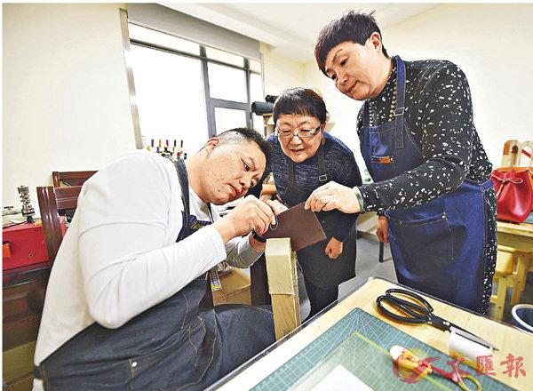 ■李麗(中)和李霞(右)在工作室指導顧客製作皮具。 資料圖片
