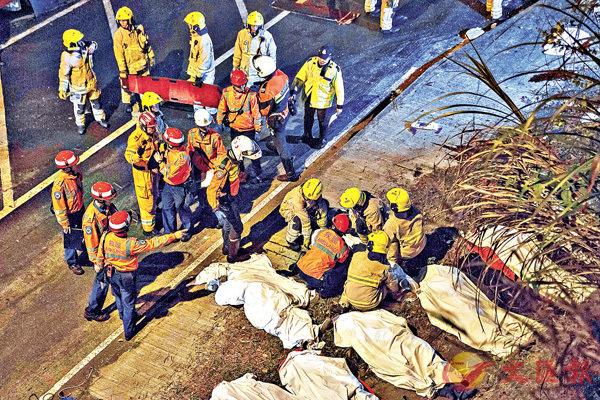 ■消防員和救護員連夜將大車禍死者的遺體搬離肇事現場。法新社