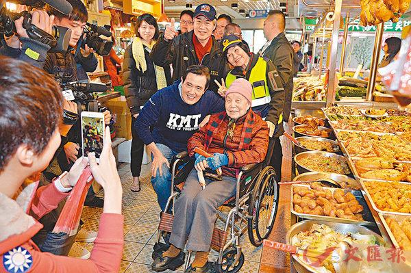 ■馬英九(前左)一路買菜,一路發放親手寫的春聯,受到鄰居們的熱情歡迎,紛紛要求合影。 中央社