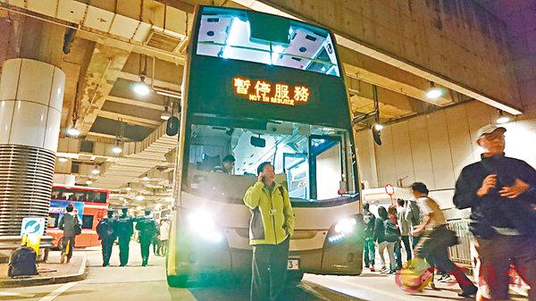 ■ 參與罷駛的九巴僱員工會主席郭志誠到尖沙咀麼地道巴士總站聲援,並擋在巴士前不讓車駛走。 香港文匯報記者顏晉傑  攝