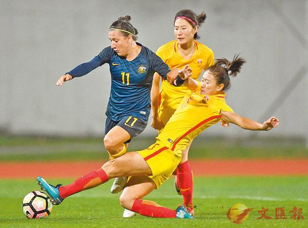 ■中國球員吳海燕(右)成功鏟走對手腳下的皮球。 新華社
