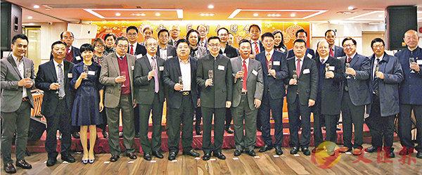 ■何靖(前排左七)出席港區潮聯新春團拜,賓主一同舉杯。香港文匯報記者繆健詩  攝