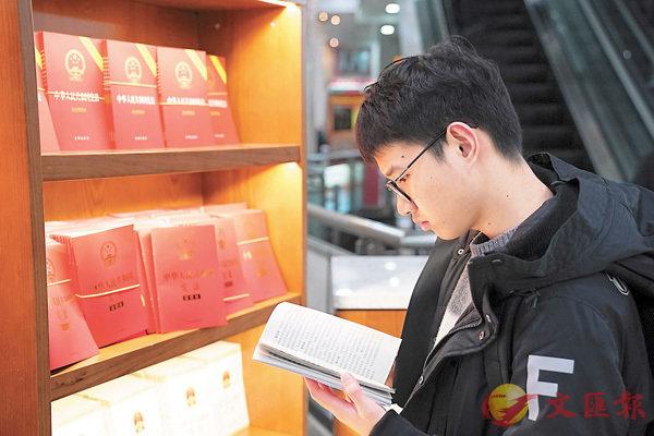 ■昨日,由法律出版社出版的最新修正版《中華人民共和國憲法》現身北京王府井書店(下圖)。圖為一名青年讀者在翻閱最新修正版《中華人民共和國憲法》。 中新社