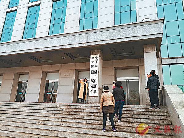 ■國務院有關機構撤銷消息一出,不少工作人員與機構牌匾合影。 香港文匯報記者馬琳  攝