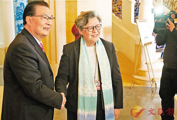 ■譚耀宗(左)與上屆人大常委范徐麗泰握手。香港文匯報記者朱朗文  攝