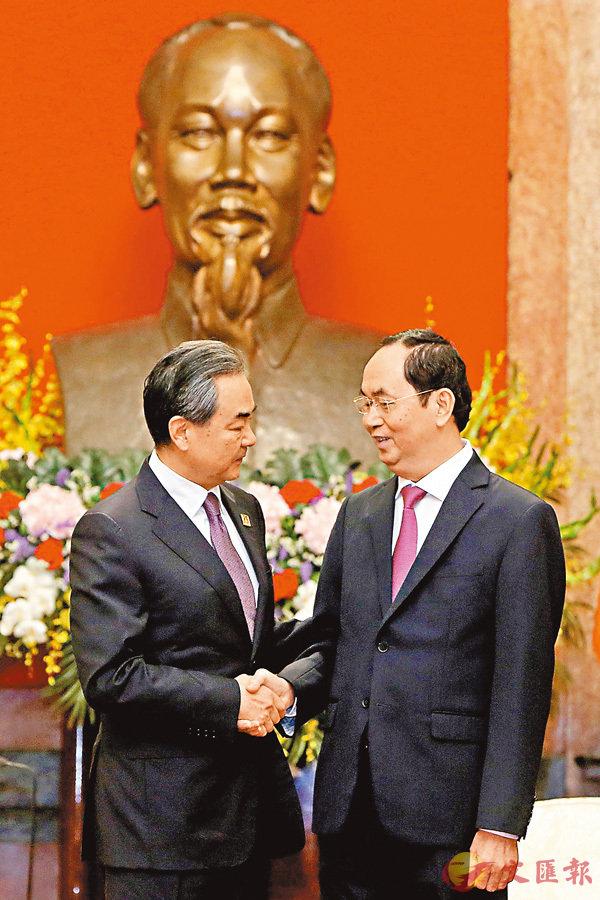 ■ 越南國家主席陳大光(右)昨日在河內會見正在對越南進行正式訪問的中國國務委員兼外交部長王毅。 法新社