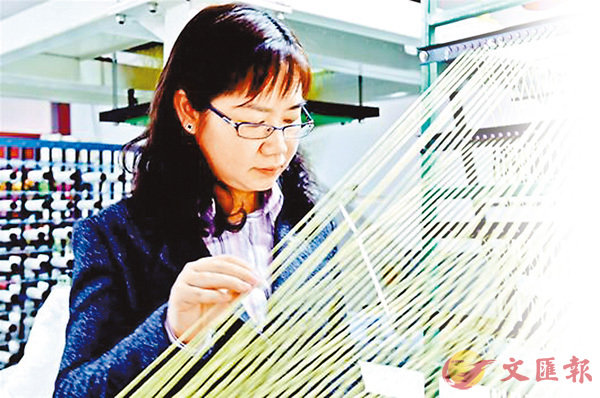 ■ 楊丹在調整織機上的防彈纖維。網上圖片