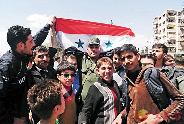 ■敘利亞警察在杜馬高舉國旗,以示無懼空襲。 新華社