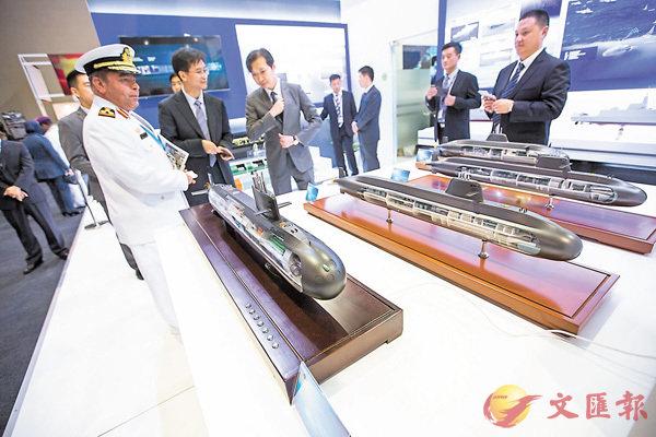 ■參展的中國企業利用模型介紹自己的技術裝備。 新華社