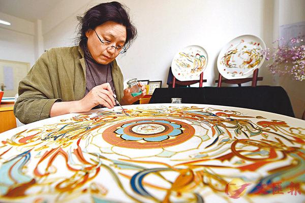 ■ 白茜原是大學音樂教師,退休後專研掐絲敦煌壁畫。圖為她在為一幅掐絲敦煌壁畫填色。 新華社