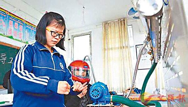 ■ 來自湖南長沙的中學生彭婧(左一)在展示獲獎作品「火險頭盔」。香港文匯報湖南傳真