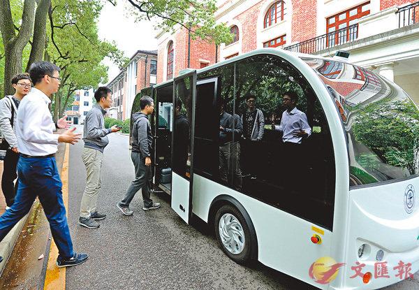 ■ 無人駕駛校巴昨日在上海交大校園實驗性運行,該校巴不僅能自主駕駛,還能自動躲避行人。圖為乘客微信叫車後準備上車。 新華社