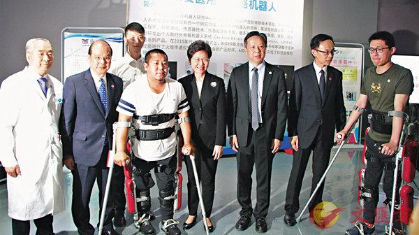 ■馬志傑(左四)向林鄭月娥(左五)清唱一曲《為愛出發》。香港代表團與外骨骼機器人研發團隊和臨床試驗者合影。 香港文匯報記者李兵 攝