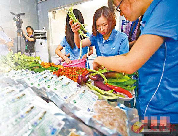 ■「月宮一號」艙門昨日再開,4位志願者帶�蚇竣滌鷎i的大豆、小麥等蔬果出艙。圖為志願者們在分揀蔬果。 網上圖片