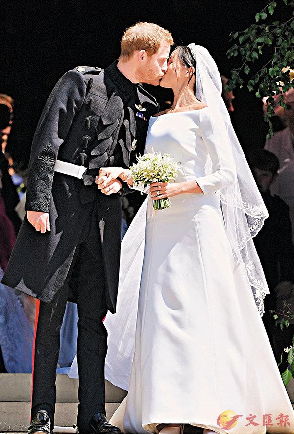 ■哈里與梅根步出教堂後,在民眾的歡呼聲下親吻。 法新社