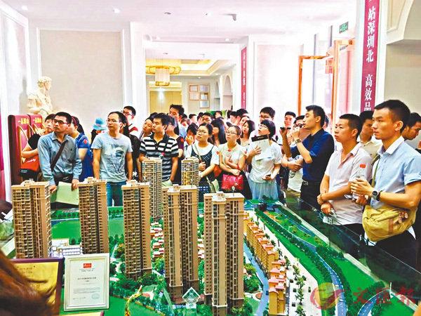 ■深圳等八個城市紛紛採取搖號購房的政策。圖為深圳購房者在了解樓盤信息。 資料圖片