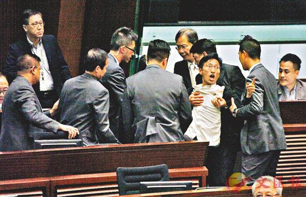 ■梁君彥把「拍�^拍得好大聲」的「議會陣線」朱凱�Y驅逐離場,多名反對派議員包圍朱凱�Y圖阻礙保安人員靠近不果,朱凱�Y被保安抬離會議廳。香港文匯報記者曾慶威  攝