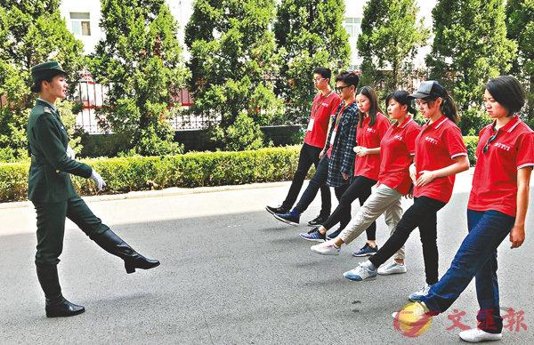 ■同學們接受儀仗隊員指導訓練試做「儀仗兵」。香港文匯報記者江鑫嫻  攝