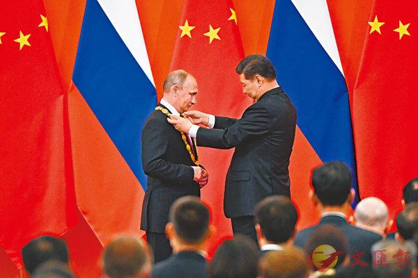 ■ 中華人民共和國「友誼勳章」頒授儀式8日在人民大會堂金色大廳舉行。國家主席習近平向俄羅斯總統普京授予首枚「友誼勳章」。 路透社