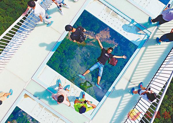 ■ 一位遊客躺在張家界大峽谷玻璃上拍照。 資料圖片