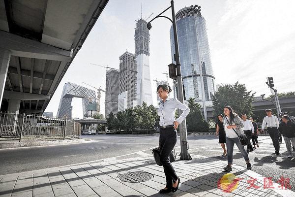 ■個人所得稅法修正案草案明確,將個稅起徵點提高至每月收入5,000元人民幣。圖為上班族走過繁忙的北京中心區。 資料圖片