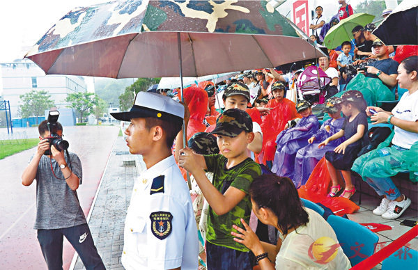 ■鄧小朋友和媽媽特意為士兵打傘擋雨,自己卻全身濕透。士兵楊先生則坦言,心中很暖。 香港文匯報記者殷翔  攝
