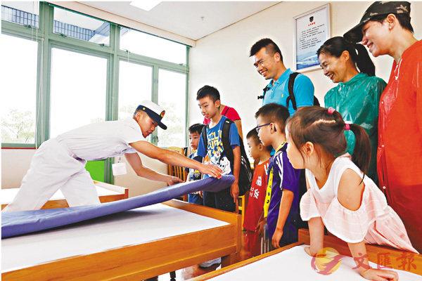■軍人示範疊成整齊方塊的被褥。 香港文匯報記者劉國權  攝