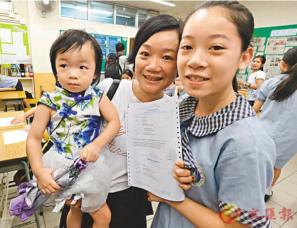 ■梁母得悉大女考入第一志願中學後立刻豎起大拇指。 香港文匯報記者梁祖彝  攝