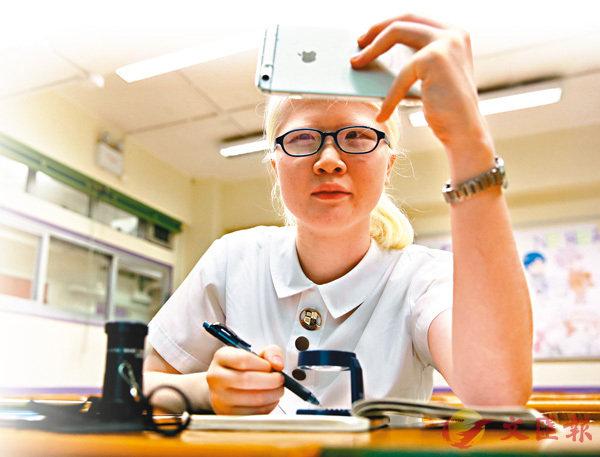 ■ 鄧麗銘患有白化症,雙眼視力只剩一成。她利用放大鏡及平板電腦等工具協助學習,終在DSE中文及經濟科考獲5**。