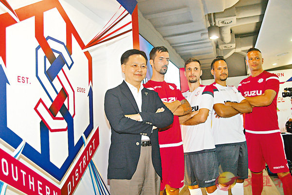 ■南區球員與班主陳文俊(左)在球隊新會徽前合影。香港文匯報記者潘志南  攝