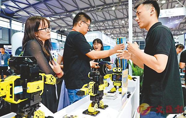 ■高峰表示,中國會按照既定的目標和節奏,積極穩妥地推進促消費的工作。圖為 2018亞洲消費電子展上,工作人員(右)向參觀者介紹一款可以講課的小型家用機械人。 資料圖片