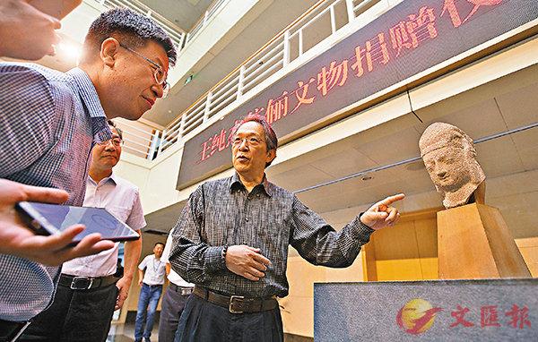 ■ 王純傑(右一)介紹石雕天王頭像的收藏經歷。 中新社