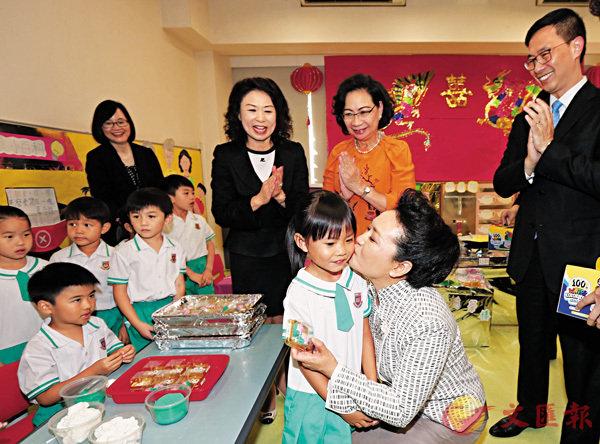 ■2017年6月29日,國家主席習近平夫人彭麗媛教授(右一)在又一村學校吻謝一位向她致送紀念品的小女生。 資料圖片