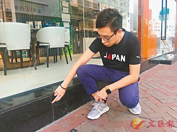 ■吳偉成展示店舖外的裂縫。香港文匯報 記者陳珈琋  攝