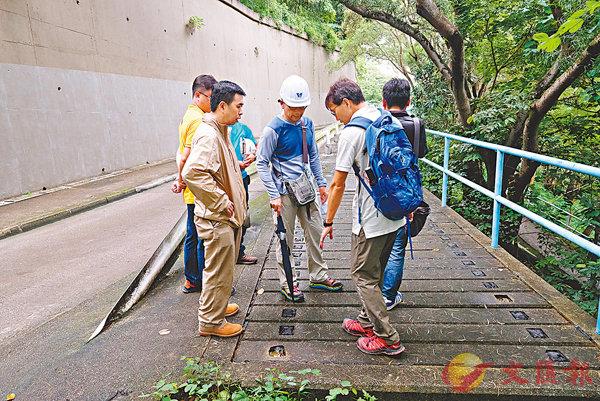 ■ 水務署職員查看路面積水情況。香港文匯報記者梁祖彝  攝