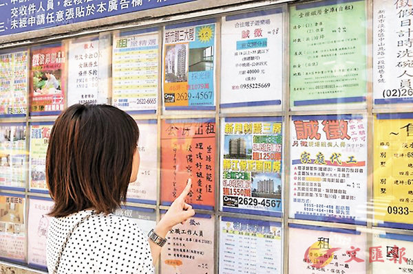 ■即使房價有所降低,年輕人仍難以買到房。圖為一年輕女子在看房價廣告。 網上圖片